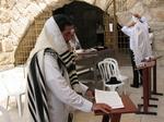 嘆きの壁の前で聖書を読むユダヤ人